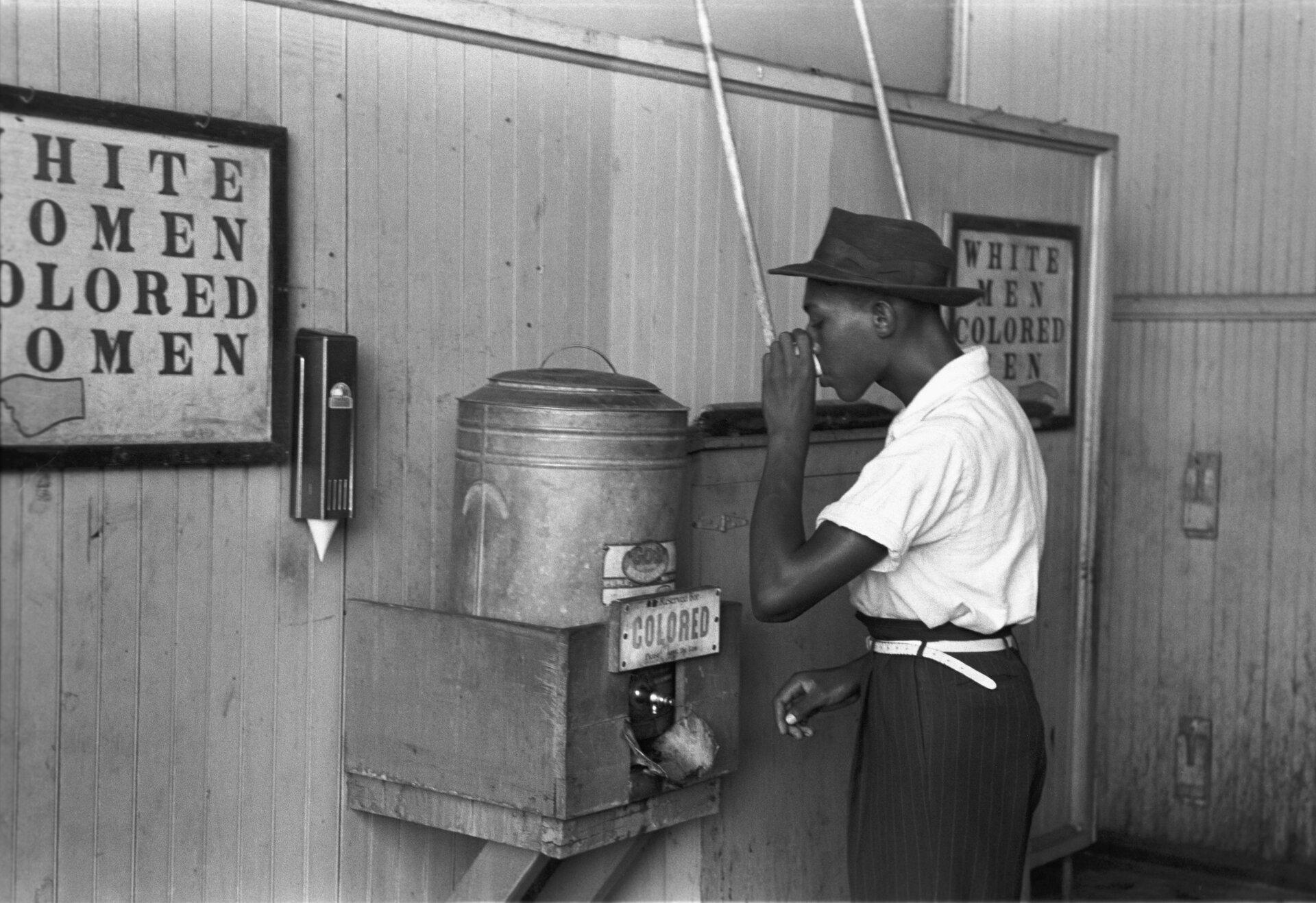 """na zdjęciu czarny mężczyzna pije wodę oznaczoną jako""""dla kolorowych"""" - zdjecie jest symbolem segregacji rasowej"""