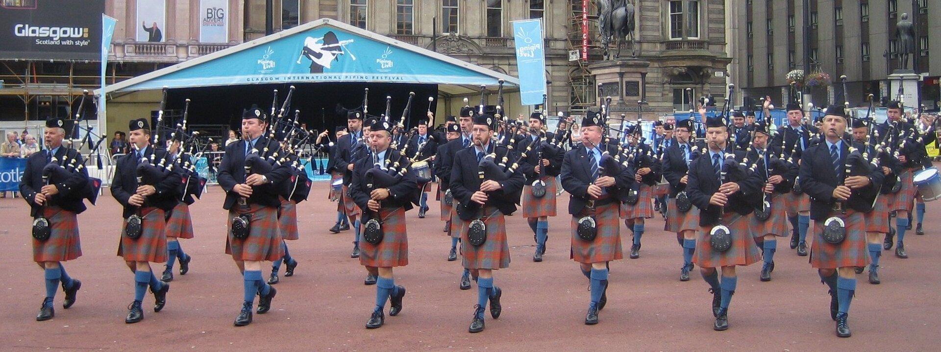 Na zdjęciu szkocka orkiestra wstrojach narodowych, mężczyźni wgranatowych marynarkach, spódnicach wczerwoną kratę. Granatowe nakrycia głowy. Grają na instrumentach dętych. Idą po placu, wtle scena plenerowa, dalej budynki.