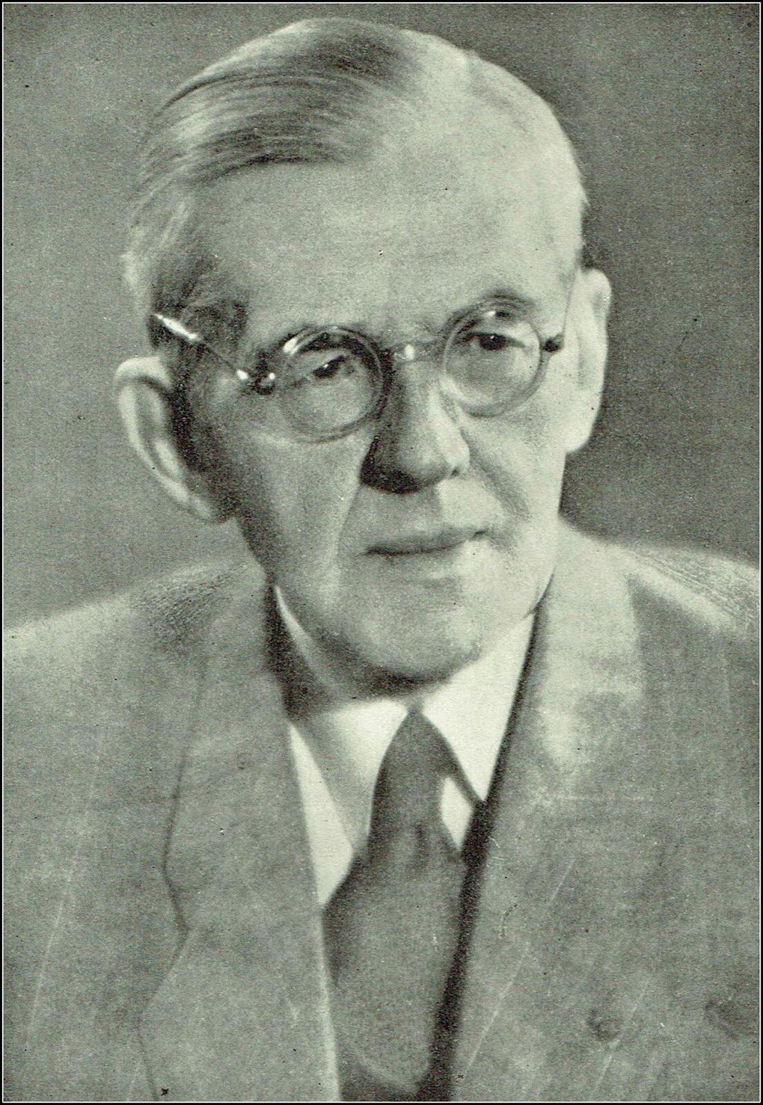 Fotografia przedstawia Adolfa Chybińskiego. Starszy mężczyzna wokularach, wkrótkich, siwych włosach. Spogląda przed siebie. Ubrany jest wbiałą koszulę ijasną marynarkę.