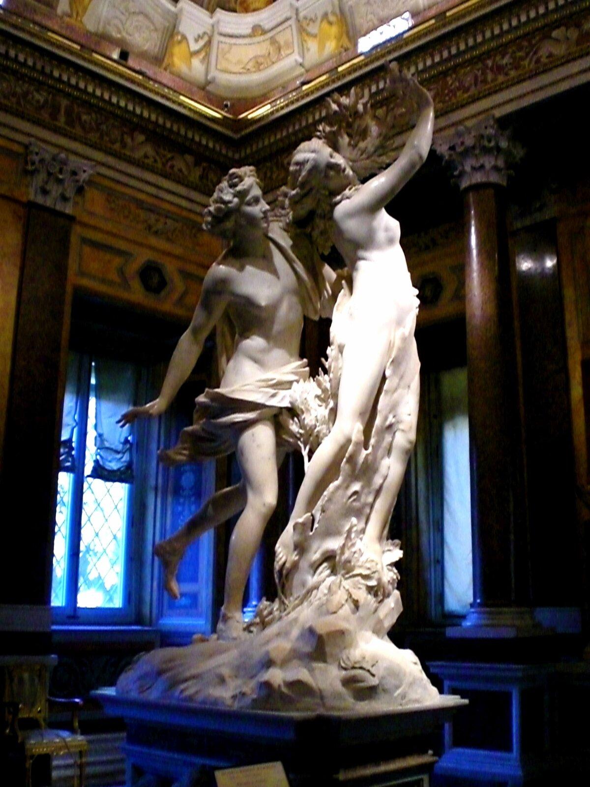 """Ilustracja przedstawia rzeźbę """"Apollo iDafne """" autorstwa Gianalorenza Berniniego. Dzieło ukazuje młodego mężczyznę biegnącego za uciekającą, długowłosą kobietą zwyciągniętymi do przodu rękoma. Postacie przedstawione są nago. Młodzieniec ma przepasane draperią biodra. Wyrzeźbiona wbiałym marmurze scena jest skomponowana dynamicznie. Artyście udało się uchwycić lekki, swobodny ruch postaci."""